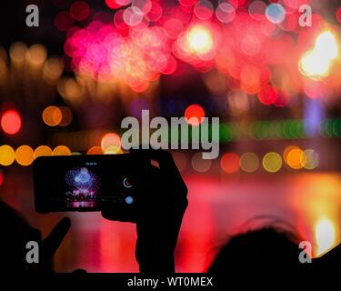 Taking Pictures Of Fireworks With Mobile Phone - Stock Photo