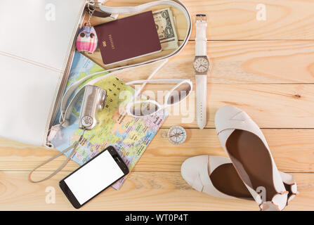 Travel concept with leather handbag, sunglasses, digital camera, world map, passport, money, compass, female shoes, smart phone and wristwatch on wood - Stock Photo