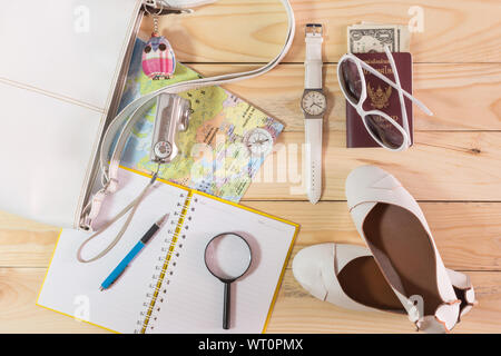 Travel concept with leather handbag, sunglasses, digital camera, world map, passport, magnifying glass, money, compass, female shoes, notepad, pen and - Stock Photo