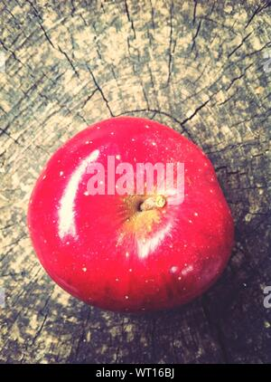 Directly Above Shot Of Red Apple On Tree Stump - Stock Photo