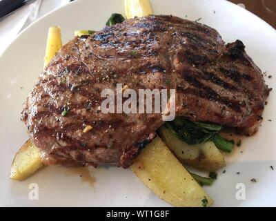 Close-up Of Rib Eye Steak And Potato With Rapini On Plate - Stock Photo