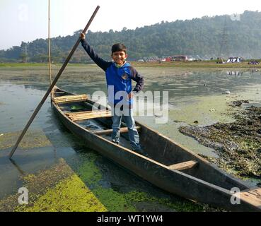Portrait Of Smiling Boy Standing On Boat Over Lake - Stock Photo