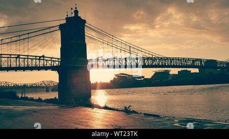 Low Angle View Of John A Roebling Suspension Bridge Over River During Sunset - Stock Photo