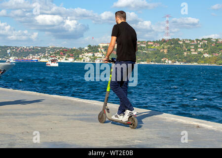 Young man riding Marti Tech, scooter rental service, rented electric scooter on the seaside. Bosphorus view with clouds in the background. - Stock Photo