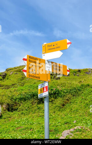 Yellow tourist sign in Bachlager, Switzerland giving distances and directions to hikers in the Swiss Alps. Popular hiking trail by Grindelwald leading to Bachalpsee. Alpine stream in the background. - Stock Photo