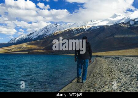 Rear View Of Man Walking By Pangong Tso By Mountains Against Sky - Stock Photo