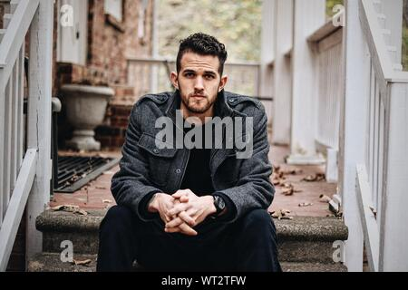 Portrait Of Serious Man Sitting On Steps At Porch - Stock Photo
