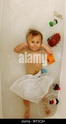 High Angle Portrait Of Boy Covering Ears With Hands In Bathtub - Stock Photo