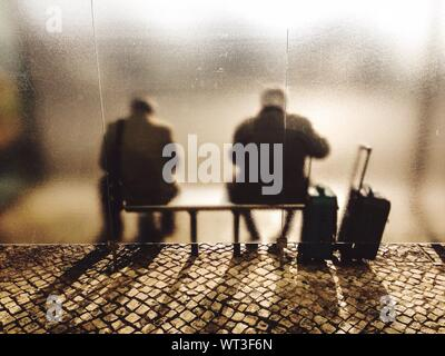 Rear View Of Two Men Sitting At Bus Stop - Stock Photo