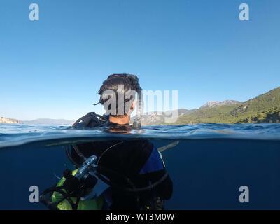 Scuba Diver In Sea Against Clear Blue Sky - Stock Photo
