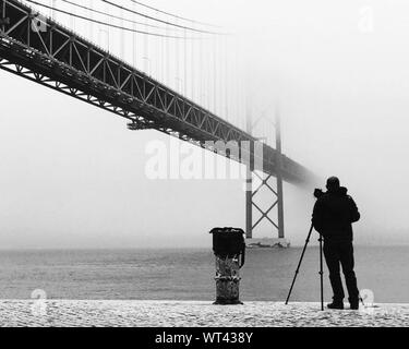 Full Length Rear View Of Photographer Standing By 25 De Abril Bridge Over Tejo River During Winter - Stock Photo