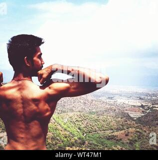 Rear View Of Shirtless Man Flexing Muscles While Standing Against Sky - Stock Photo