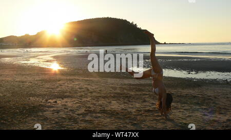Young Woman Doing Handstand At Beach Against Clear Sky During Sunset - Stock Photo