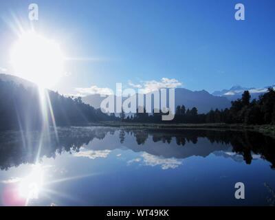 Sun Shining Over Lake Against Sky - Stock Photo