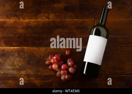 Flat lay mockup with wine bottle and red grape. From above image with copy space - Stock Photo