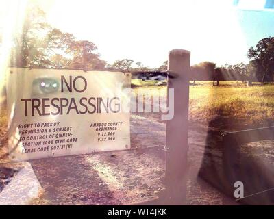 Double Exposure Of Woman Face Against Sign On Fence - Stock Photo