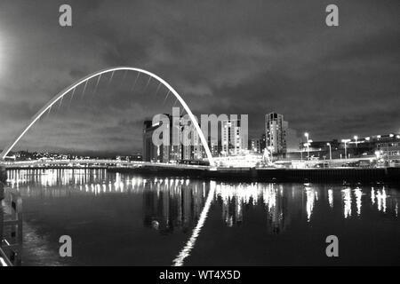 Gateshead Millennium Bridge Over Tyne River By Illuminated City At Night - Stock Photo