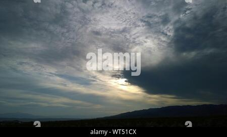 Low Angle View Of Cloudy Sky Over Silhouette Mountains - Stock Photo