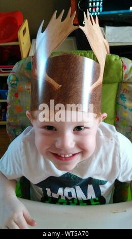 Portrait Of Smiling Cute Boy Wearing Artificial Crown At Home - Stock Photo