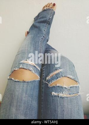 Low Section Of Woman Wearing Torn Jeans - Stock Photo