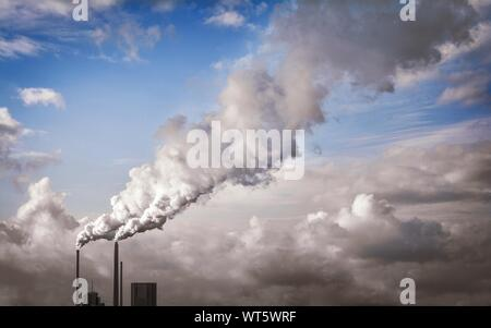 Low Angle View Of Smoke Emitting From Smokestacks Against Sky - Stock Photo