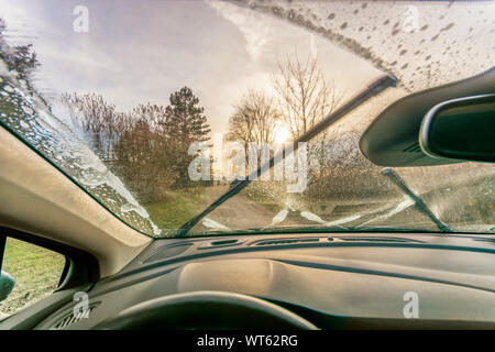 Cleaning the glass with antifreeze and windscreen wipers for a clear view - Stock Photo