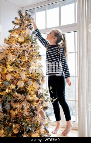 Beautiful little girl dressed in pajamas places a star on top of Christmas trees - Stock Photo