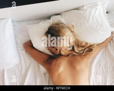 High Angle View Of Shirtless Woman Lying On Bed At Home - Stock Photo