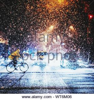 Person Riding Bicycle In Snowfall During Night - Stock Photo