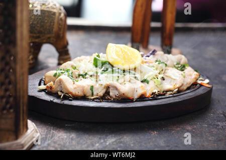 Chicken malai tikka on a hot dish - Stock Photo