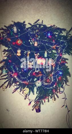 Christmas Wreath With Ornaments Hanging On Wall - Stock Photo