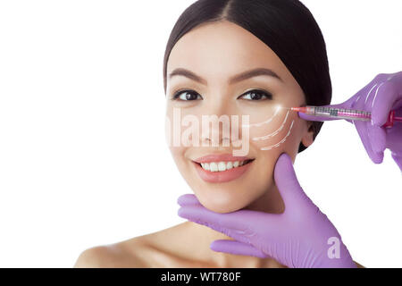 Beautiful asian woman advertising lifting injections. Perfect female face showing anti age injection isolated on white - Stock Photo