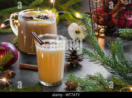 Apple cider cocktail with cardamom and star anise on black table with fir tree branches. Close up. - Stock Photo