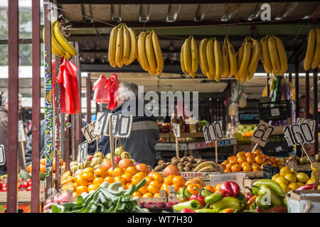 BELGRADE, SERBIA - NOVEMBER 1, 2014: Fruits and vegetables, mainly bananas, hanging for sale on a stand of Kalenic Pijaca, one of the main green marke - Stock Photo