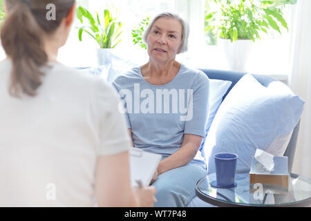 Talk therapy concept: female doctor talking with her senior patient about her problems during a counseling session. - Stock Photo