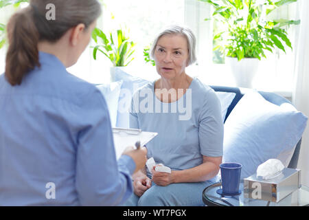 Talk therapy concept: therapist talking with her mature client about her current issues during a counseling session. - Stock Photo