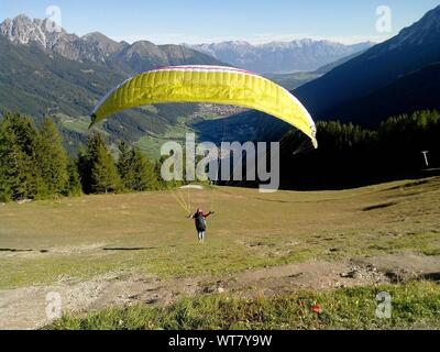 Paraglider Landing On A Grassy Field Against Mountains - Stock Photo