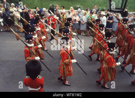 1960s, Windsor, England, UK. Noble Order of the Garter, people watching the procession taking place as Yeoman Guards match outside the castle to Stt George's Chapel for the annual Garter Service. Founded in 1348 it is the oldest British order of Chivalry. - Stock Photo