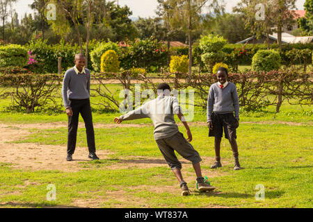 Imani Junior Academy, Nanyuki, Laikipia county, Kenya – June 13th, 2019: Candid photograph of young school children playing football in field at Imani - Stock Photo