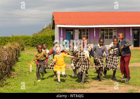 Imani Junior Academy, Nanyuki, Laikipia county, Kenya – June 13th, 2019: Candid photograph of young school children playing with a white girl who was - Stock Photo