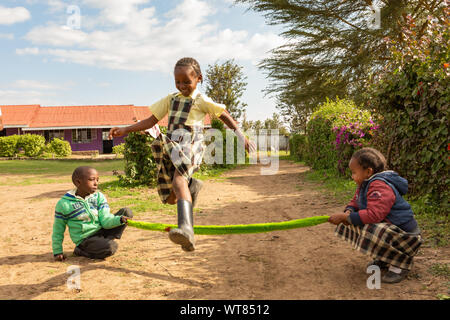 Imani Junior Academy, Nanyuki, Laikipia county, Kenya – June 13th, 2019: Candid photograph of young school children skipping with an improvised rope o - Stock Photo