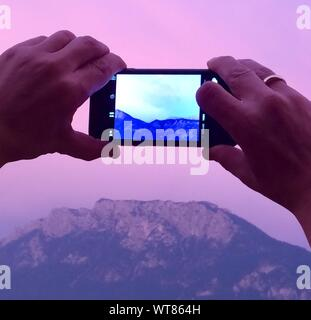 Cropped Image Of Hands Holding Camera Against Mountain - Stock Photo