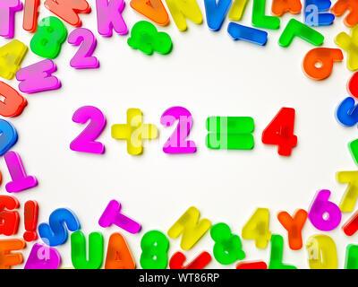 Plastic multi coloured fridge magnet alphabet showing 2+2 = 4 math maths - Stock Photo