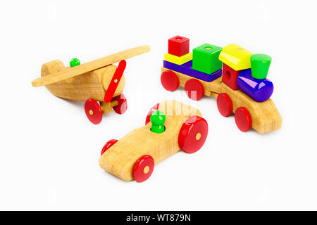 Wooden plane, train and racing car, a selection of childrens wooden toys on a white background - Stock Photo