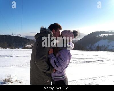 Couple Kissing On Snow Covered Field Against Clear Blue Sky Stock Photo