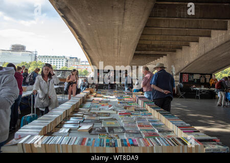 People browsing and buying books for sale on the South Bank Book Market under Waterloo Bridge, London. - Stock Photo