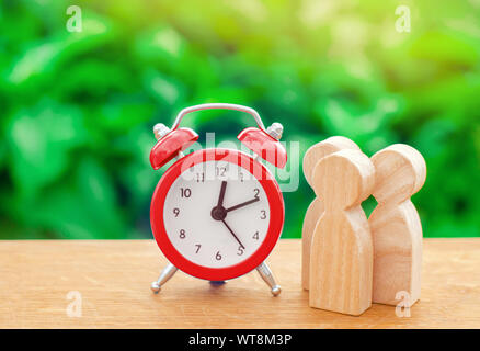 Three wooden human figures standing next to a red alarm clock on a nature background. Time concept. Business, Hourly payment. Man hours. Planning. min - Stock Photo