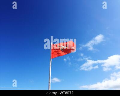Low Angle View Of Flag Against Blue Sky - Stock Photo