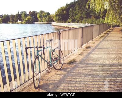 Bicycle Parked By Railing And Lake On Sunny Day - Stock Photo