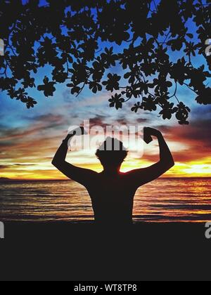 Rear View Of Silhouette Man Flexing Muscles While Standing At Beach Against Sky During Sunset - Stock Photo